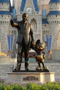 Walt Disney standing with Mickey Mouse