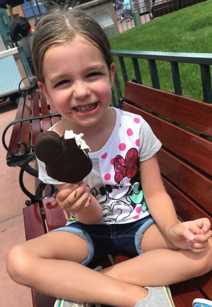 Girl enjoying Mickey Ice Cream Bar at Disney