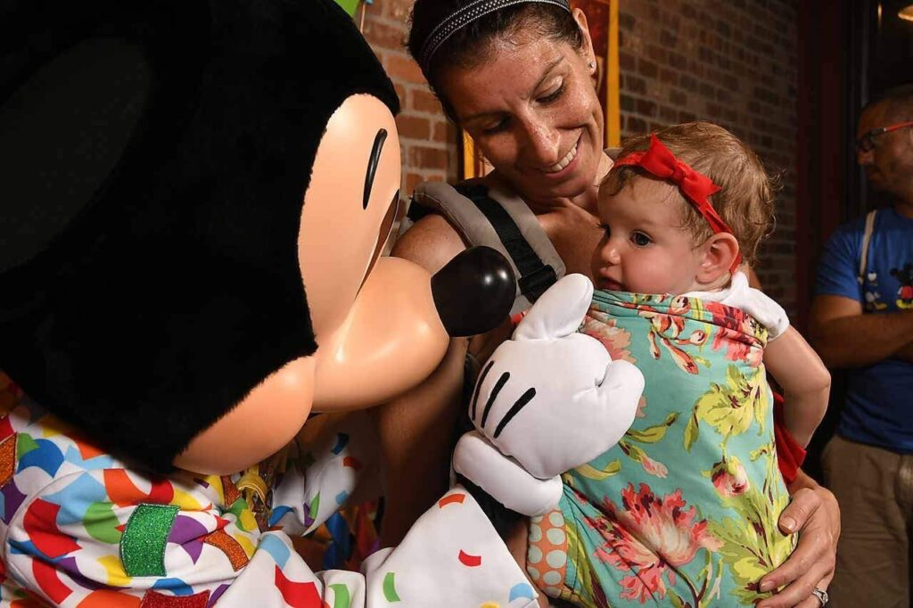 Mom and daughter meeting Mickey Mouse